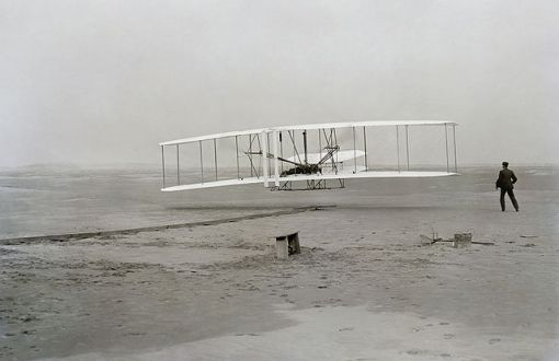 Wright Brothers First Flight, December 17, 1903. Orville piloting. Wilbur at the wing.